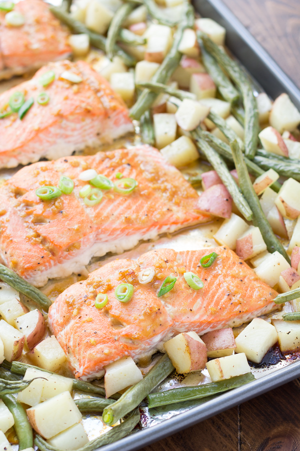 four salmon fillets on baking sheet with green beans and potatoes