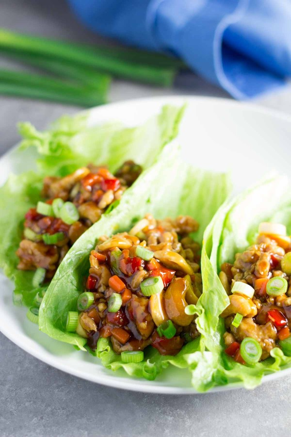 Close up of cashew chicken lettuce wraps on a white plate.