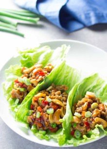 Chicken lettuce wraps with cashews on a white plate with green onions in the background.