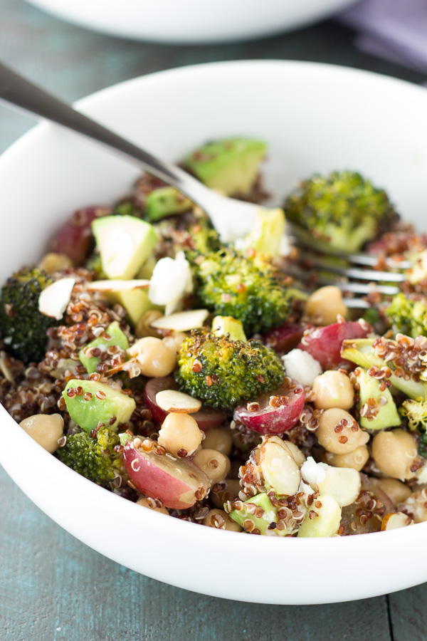 vegetarian lunch in a white bowl with sliced broccoli, quinoa, sliced grapes, chickpeas, avocado and feta