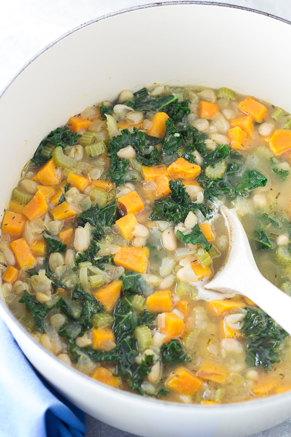 soup cooking in a dutch oven with white beans, butternut squash and kale