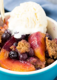 Crockpot peach cobbler with blueberries, topped with vanilla ice cream.