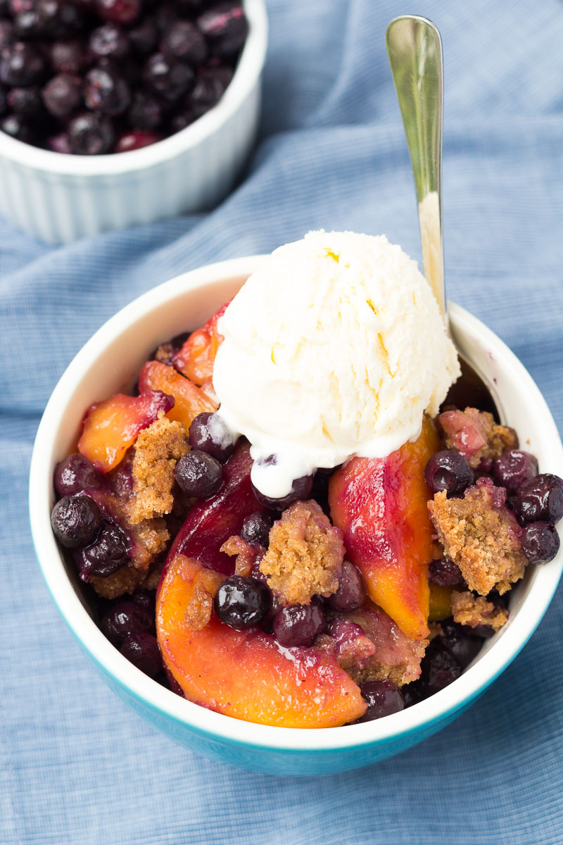 Blueberry peach cobbler in a bowl served with ice cream.