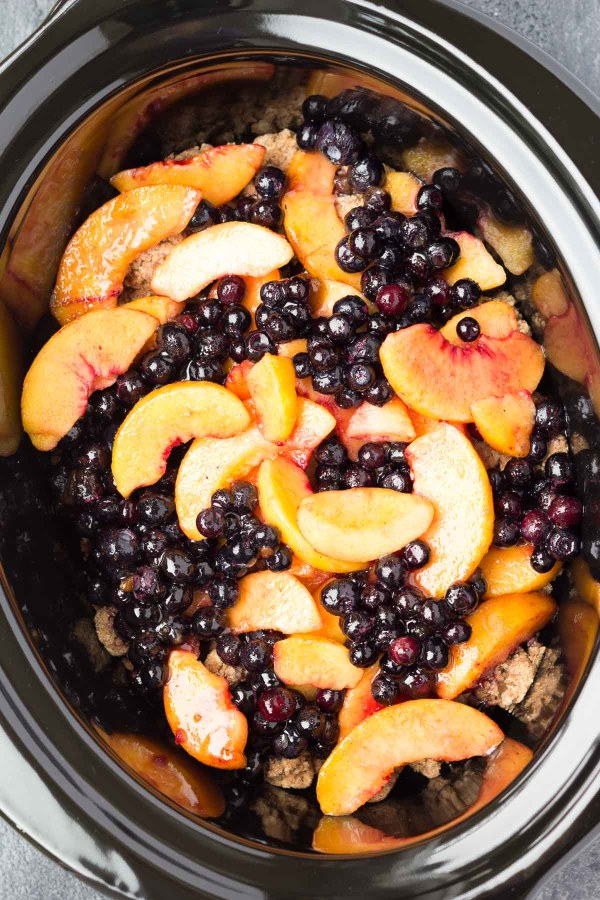 A healthier Slow Cooker Blueberry Peach Cobbler recipe, full of juicy berries and peaches and a touch of brown sugar. This easy dessert is made entirely in your crock pot!
