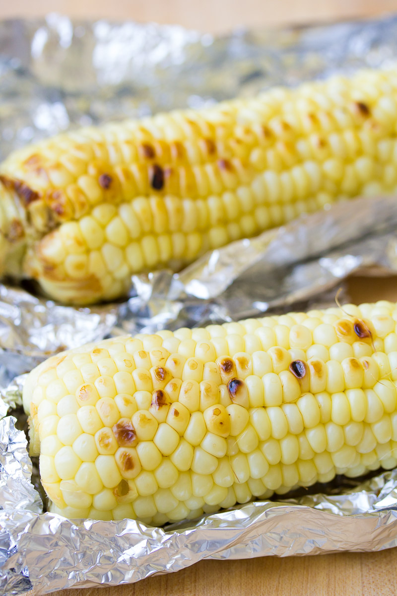 Grilled corn on the cob sitting on top of foil.