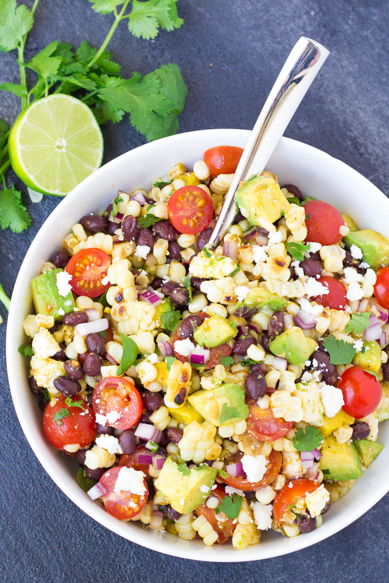 Black bean and corn salad in a white bowl with lime and cilantro next to the bowl.