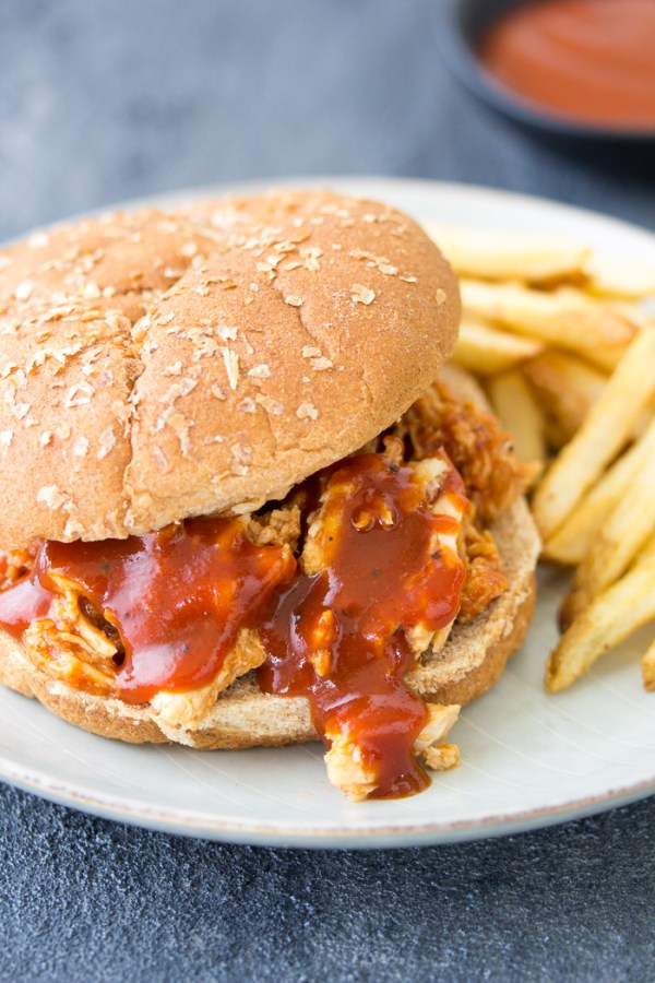 Crockpot BBQ Chicken Sandwich on a plate with french fries.