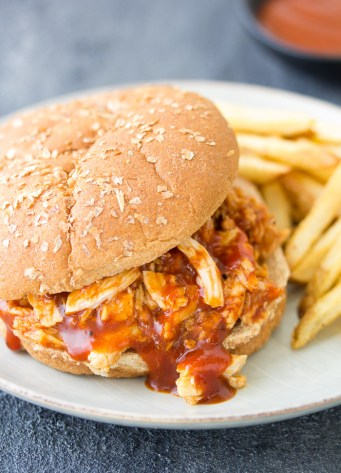 Slow Cooker BBQ Chicken on a burger bun. This easy crockpot recipe is perfect for sandwiches, salads, and more!
