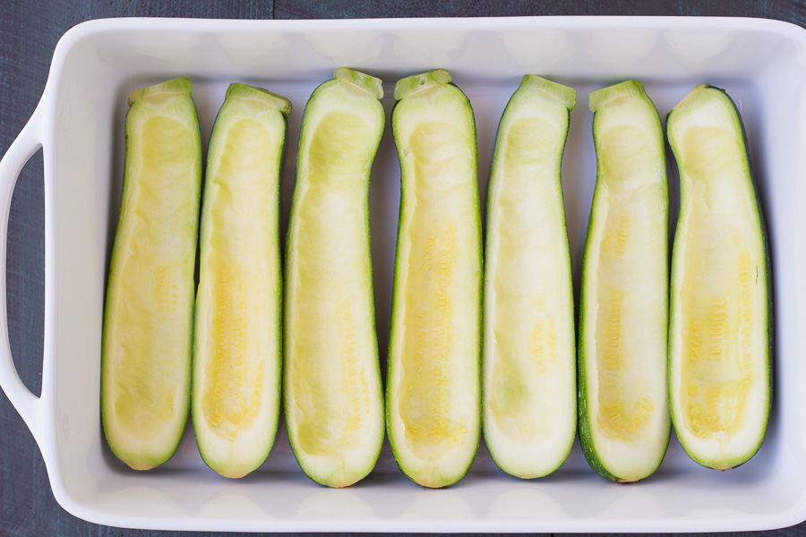 prepared zucchini halves lined up in white baking dish