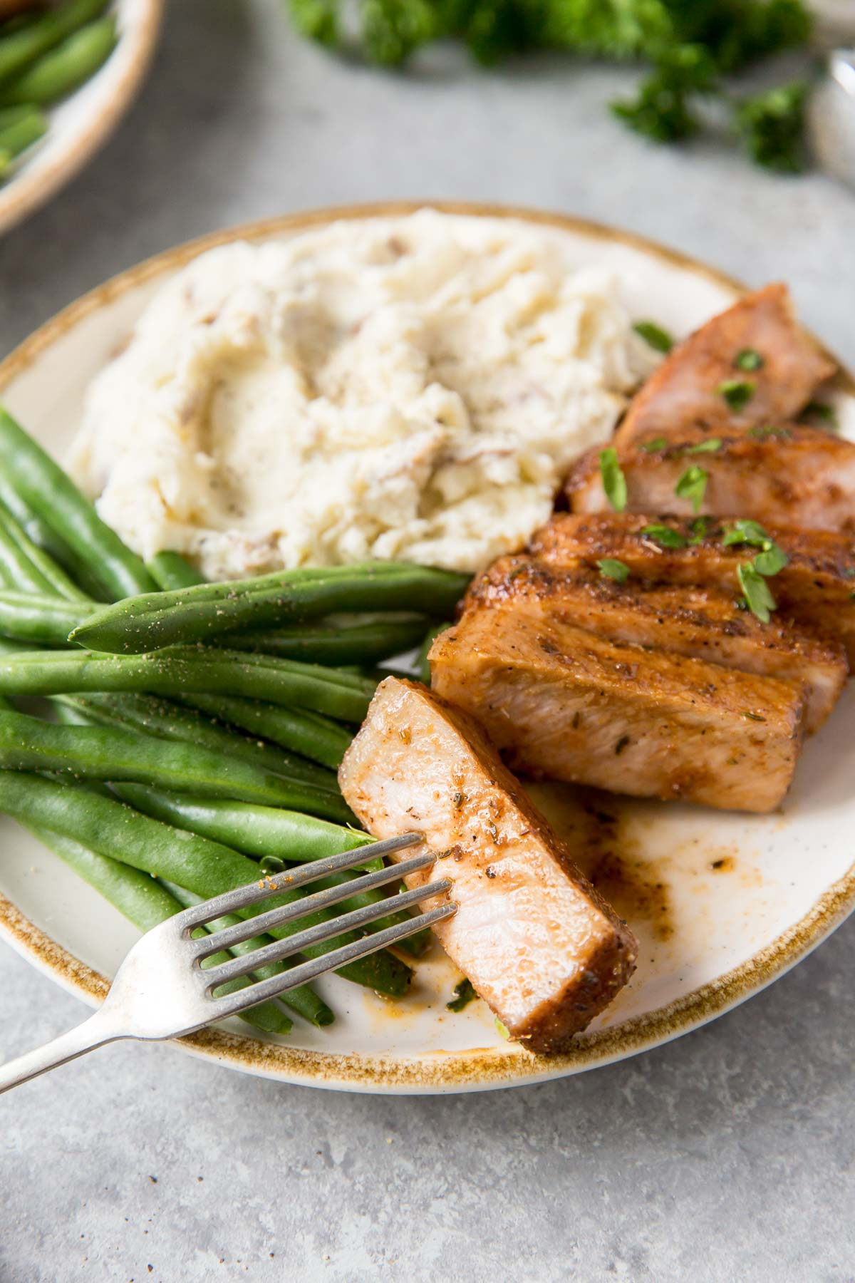 baked pork chop served with green beans and mashed potatoes