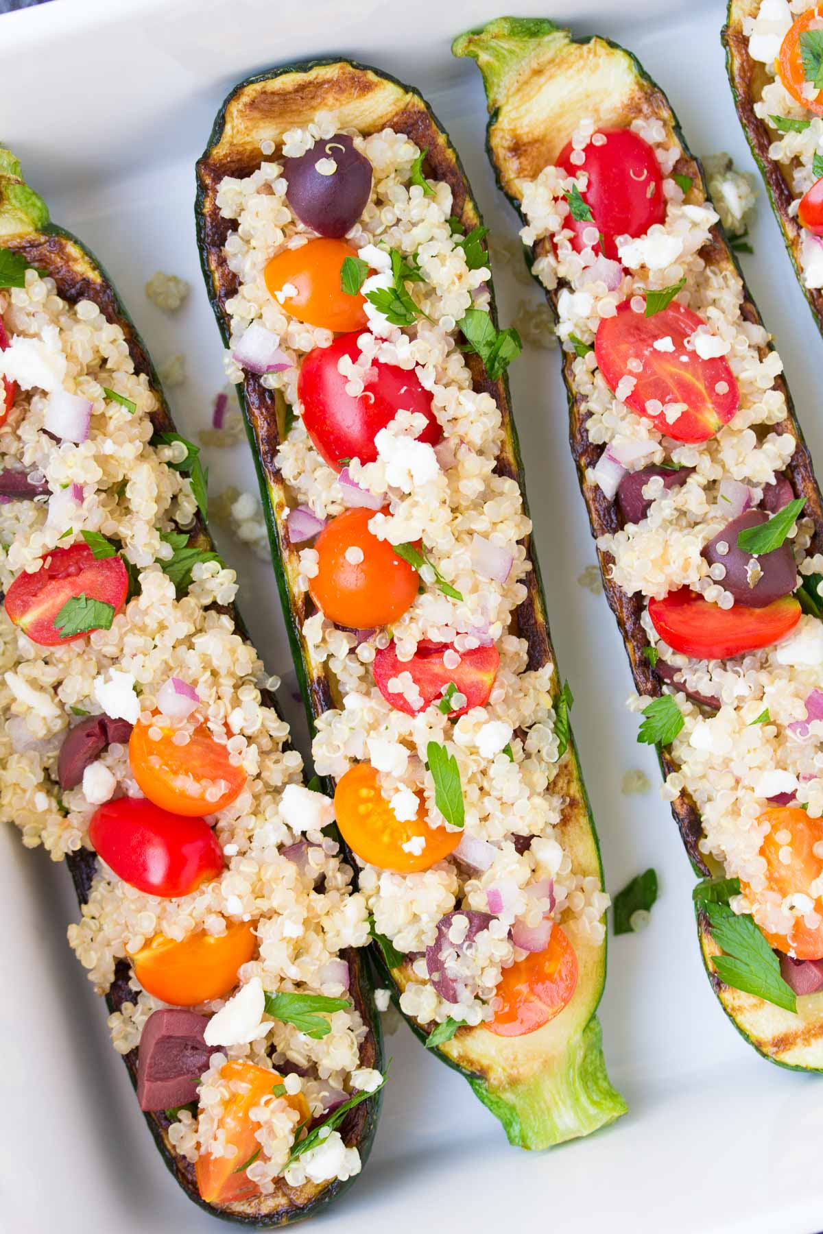 Zucchini Boats stuffed with olives, tomatoes, and feta.