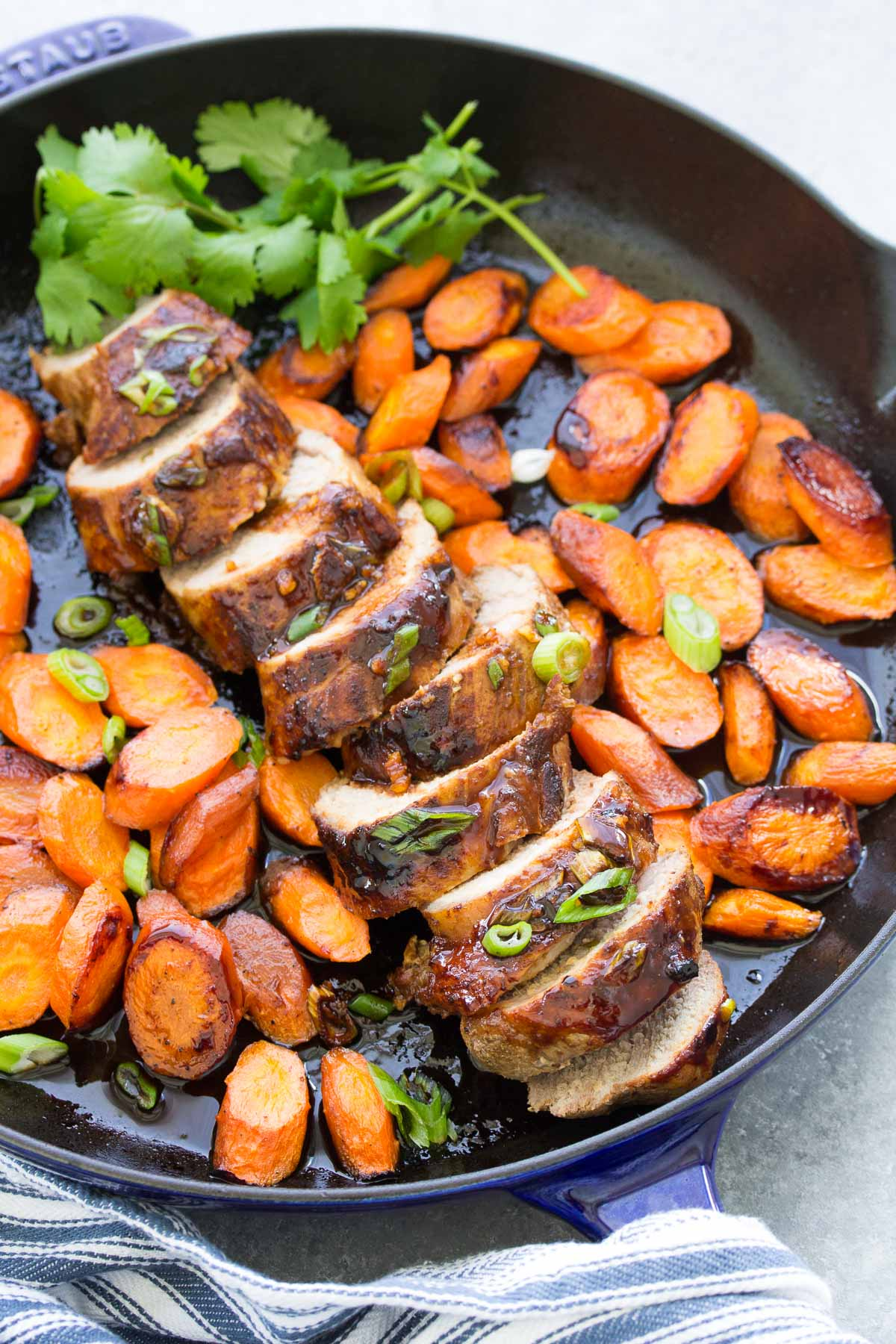 honey hoisin pork tenderloin with carrots in a cast iron skillet