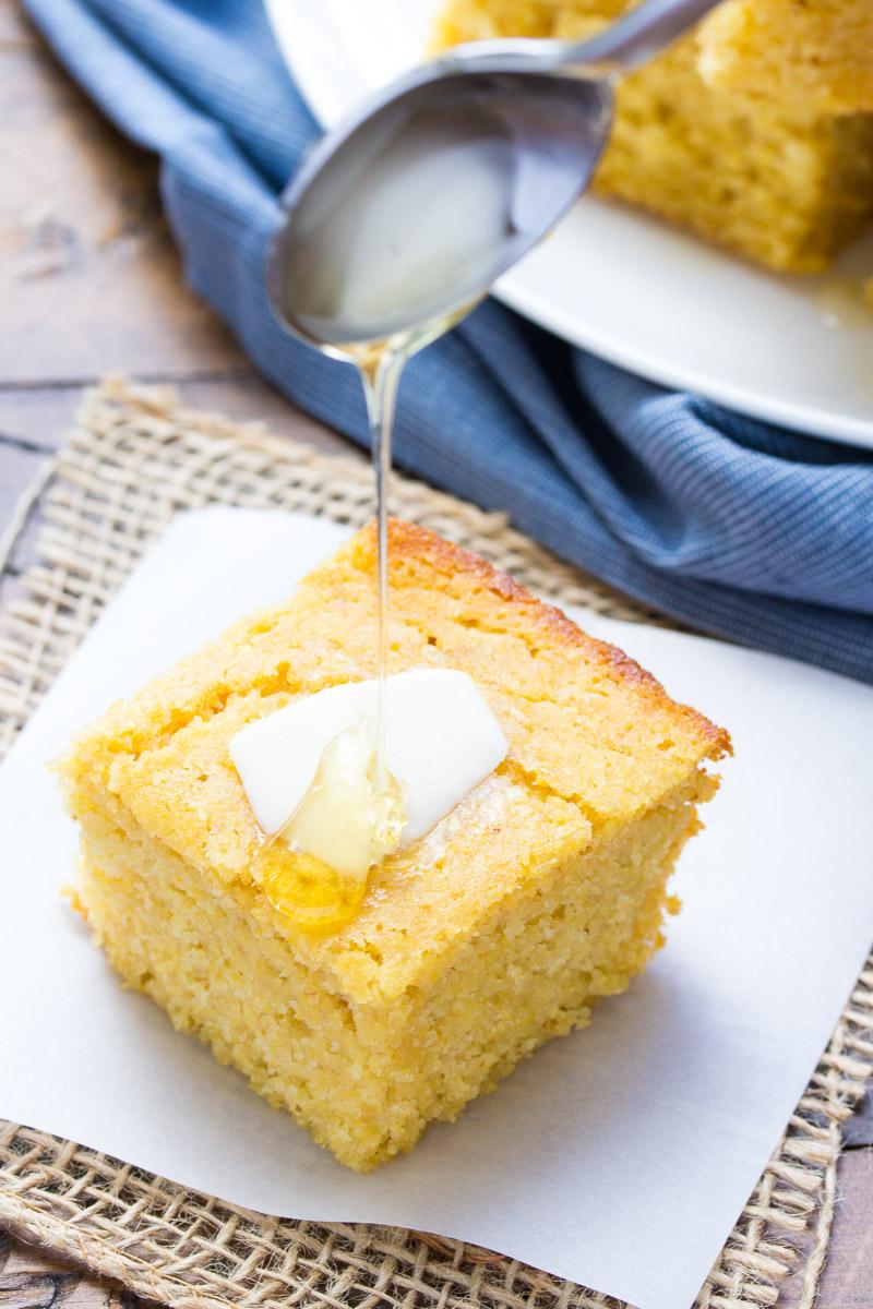 drizzling honey onto cornbread slice