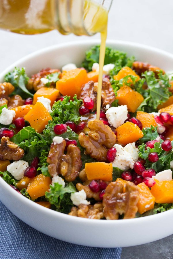Our FAVORITE kale salad! Butternut squash and pomegranate kale salad with spiced honey walnuts and a maple dressing. SO YUMMY for lunch or your holiday dinner! | www.kristineskitchenblog.com