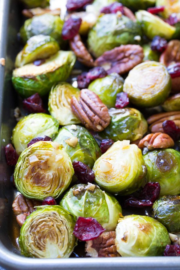 Roasted brussels sprouts with cranberries and pecans on a baking sheet.