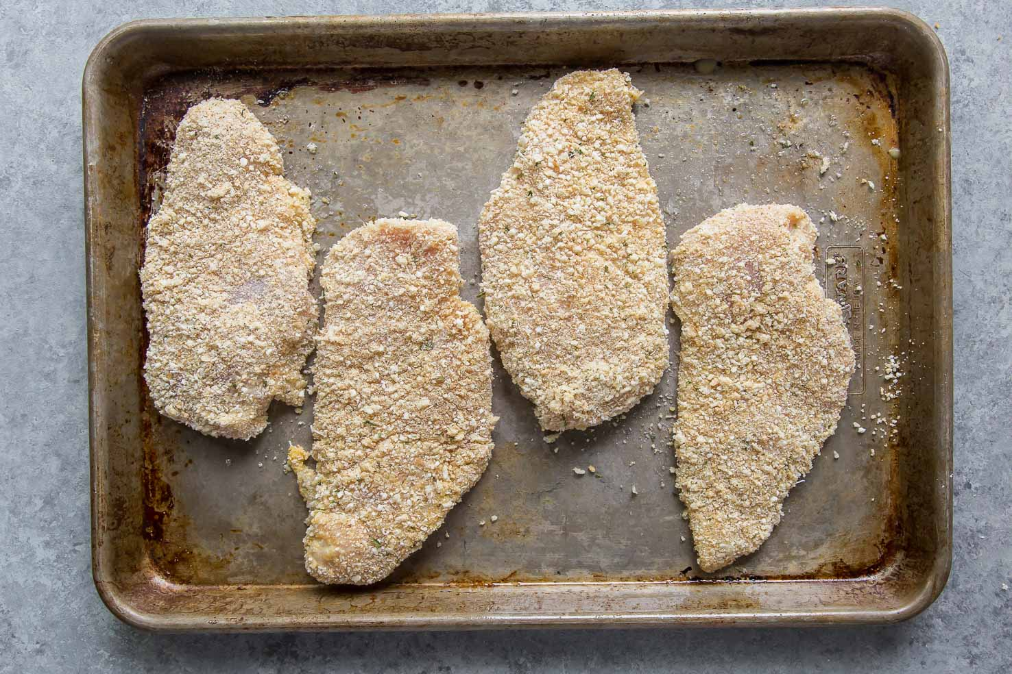 breaded chicken on baking sheet
