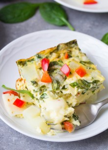 A slice of vegetarian breakfast casserole with a fork.