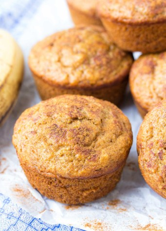 Healthy banana muffins on parchment paper with cinnamon sprinkled around.