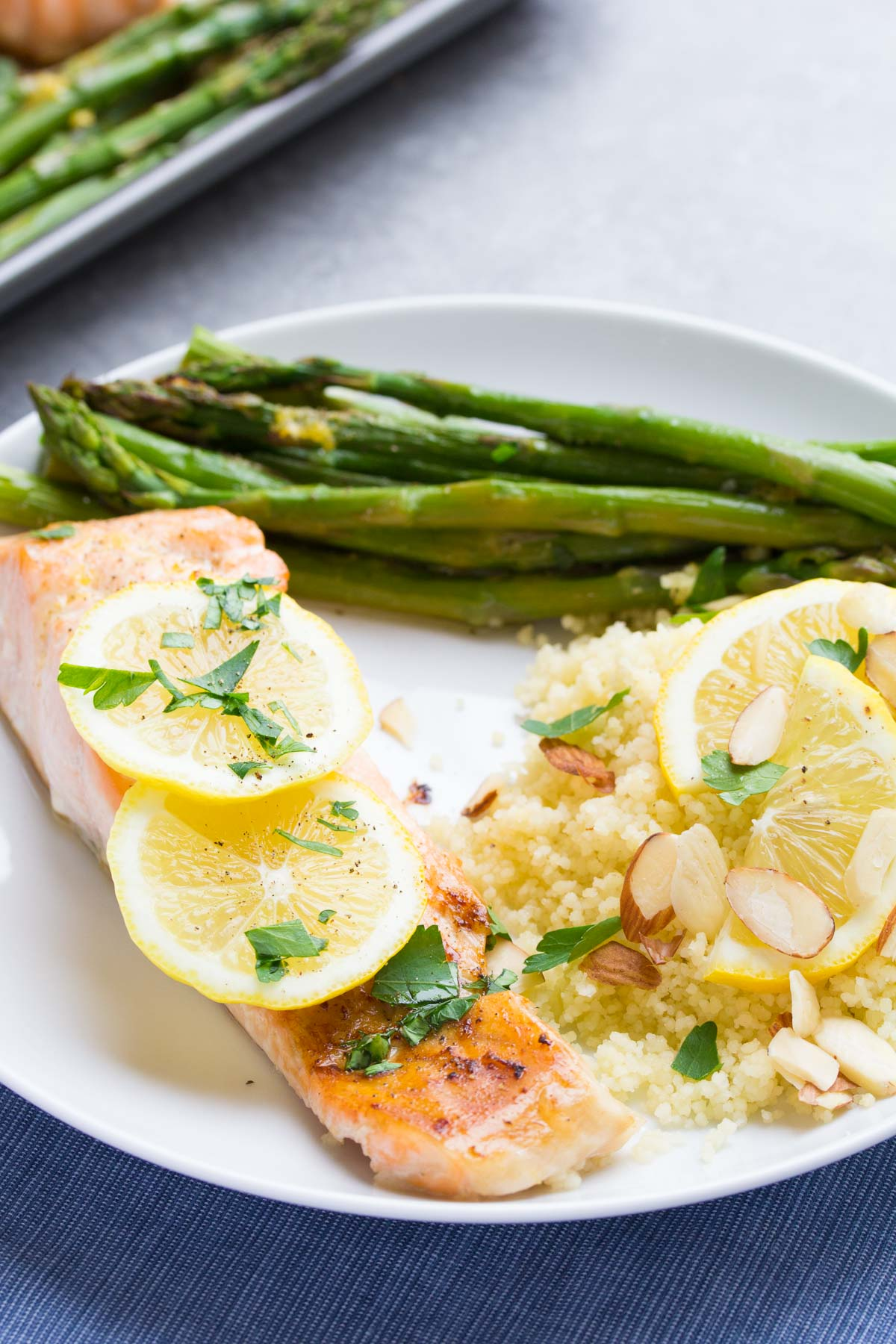 lemon garlic salmon with asparagus and couscous ready to eat on a white plate topped with lemon slices