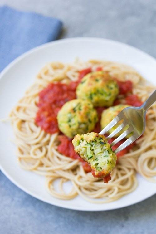 Baked Zucchini Meatball on a fork, with a plate of pasta in the background.