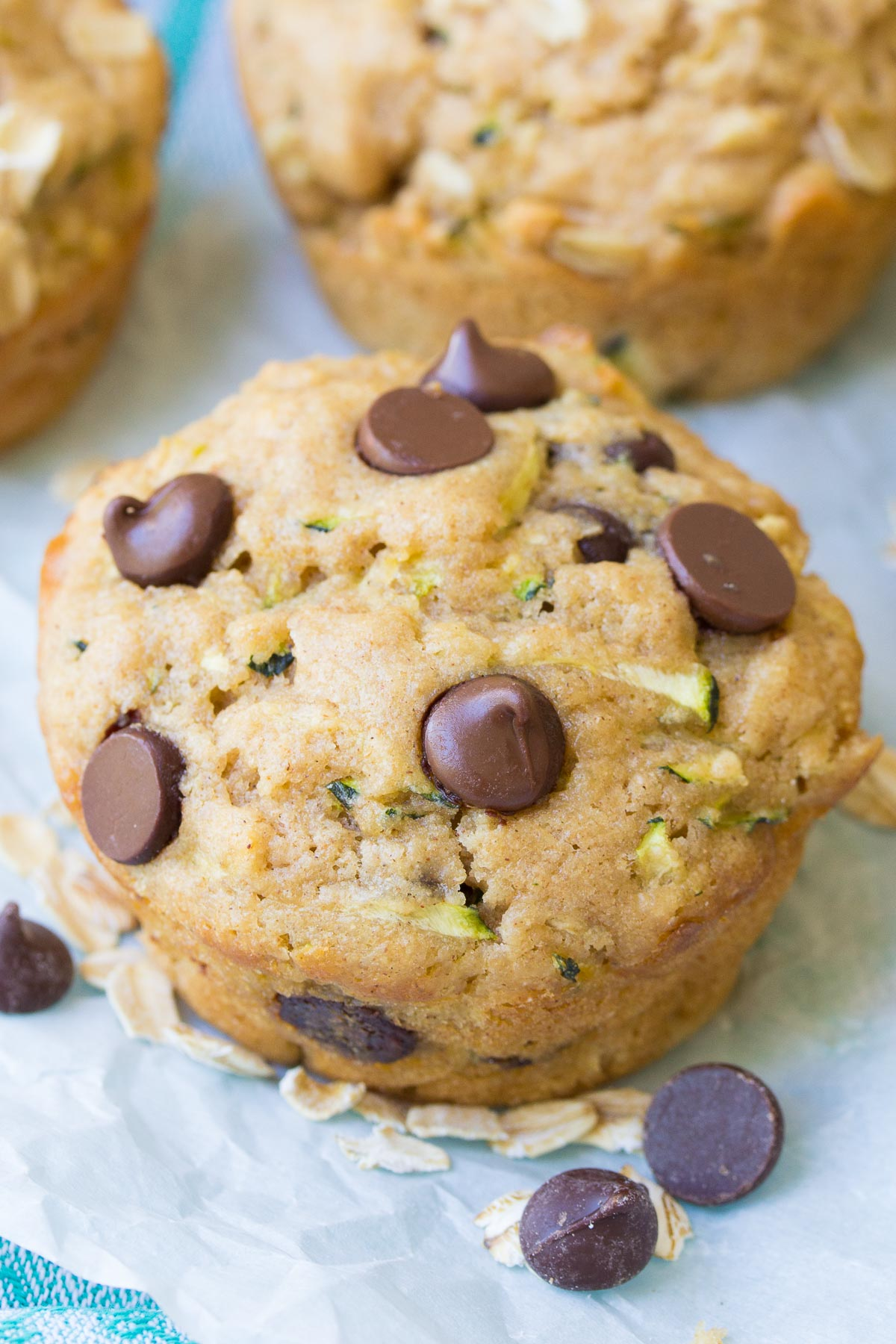 Close up of a muffin after baking, with chocolate chips around.