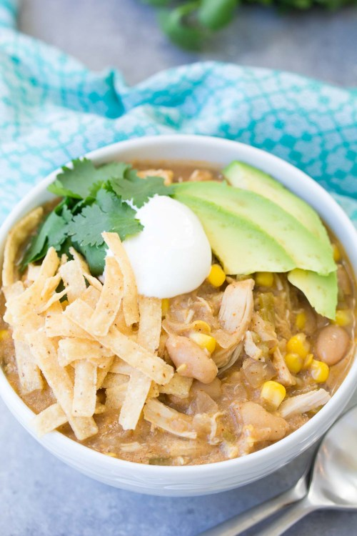 white chicken chili in a bowl with tortilla strips and garnish