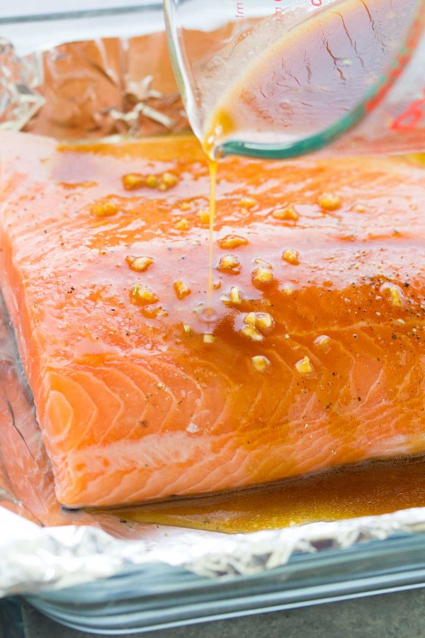 Pouring honey garlic sauce on a salmon filet.