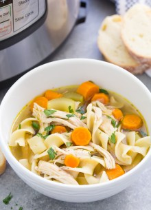Instant Pot Chicken Noodle Soup in a white bowl with a pressure cooker in the background.