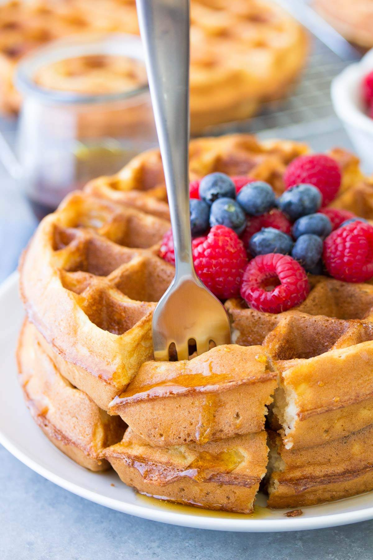 stack of two waffles with a fork standing up in a bite of waffle