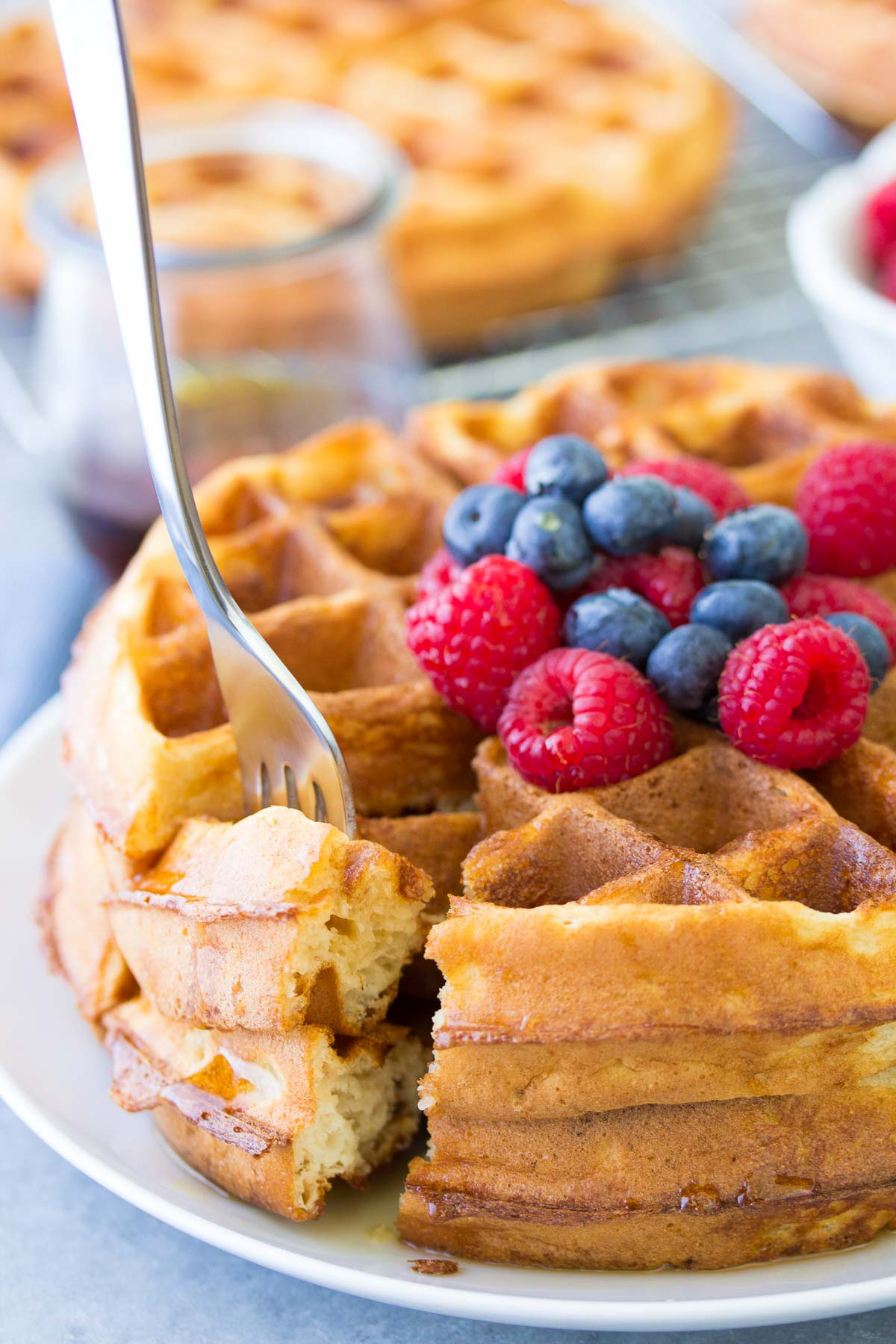 bite of waffle on a fork, showing fluffy waffle insides