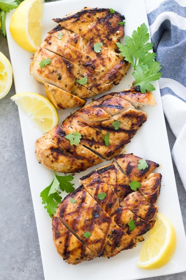three grilled chicken breasts sliced on a white rectangular serving platter