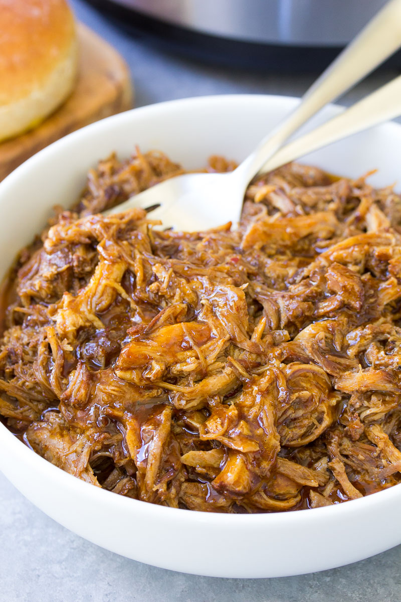 Shredded BBQ pulled pork in a white bowl.