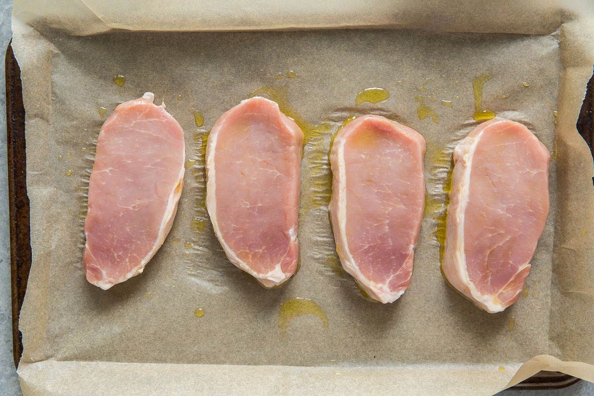 preparing uncooked pork chops with olive oil on baking sheet
