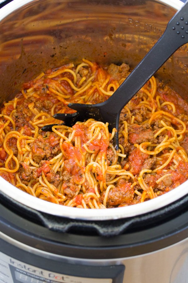 Instant Pot Spaghetti inside the Instant Pot with a serving spoon