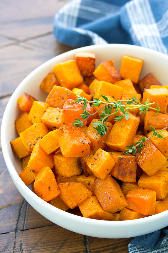 Roasted cubed butternut squash in a white bowl