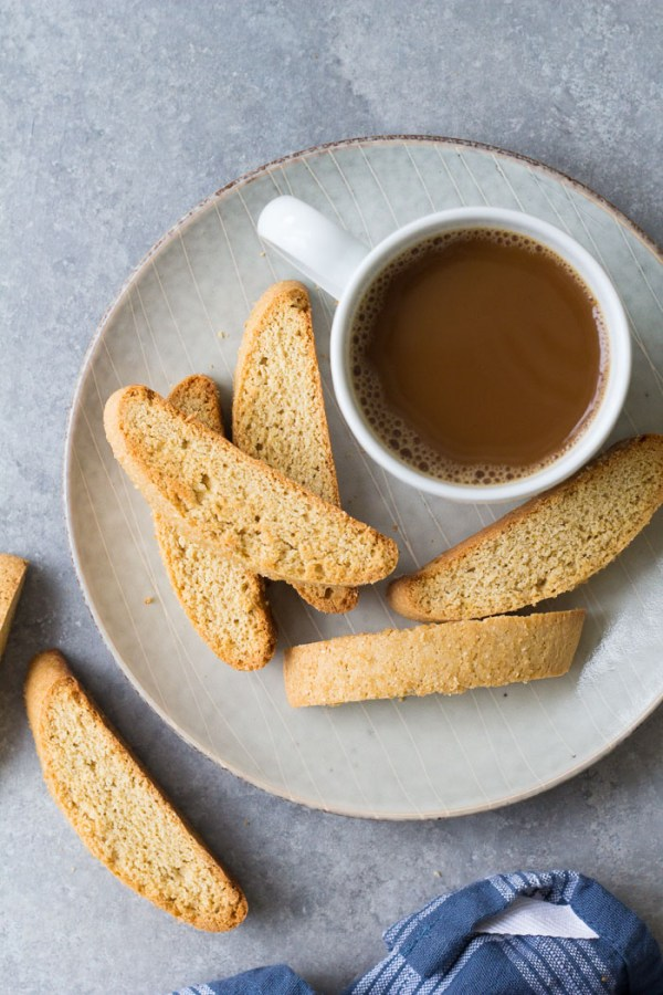 Biscotti on a plate with a cup of coffee.