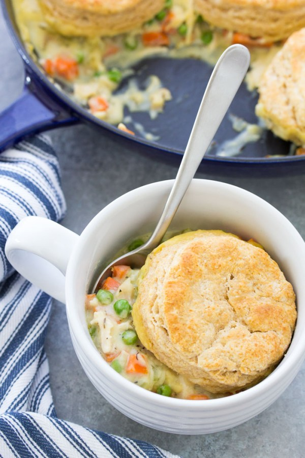 Chicken Pot Pie with Biscuits in a serving dish with a spoon.