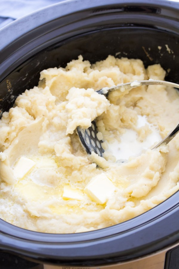 Mashed potatoes in a crock pot with a potato masher and butter.
