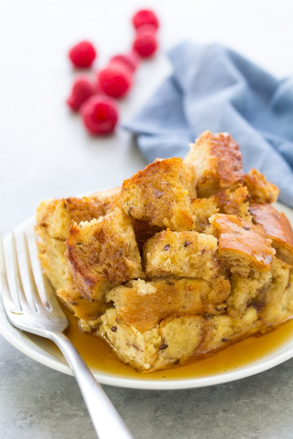 A slice of baked french toast casserole on a plate with syrup
