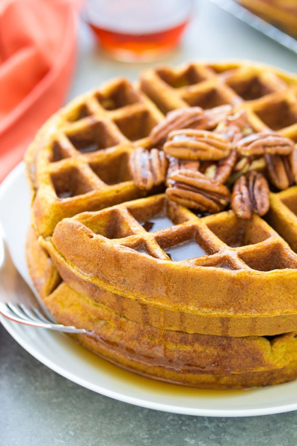 Healthy pumpkin waffles with pecans and maple syrup.
