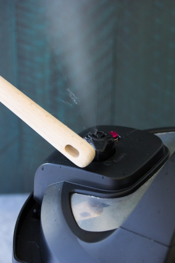 Opening the Instant Pot steam release valve with the handle of a wooden spoon.