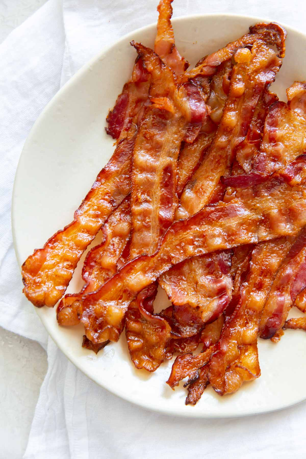 baked bacon slices stacked on a plate