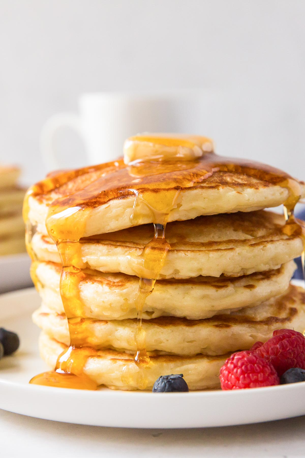 close up of stack of pancakes with butter and syrup