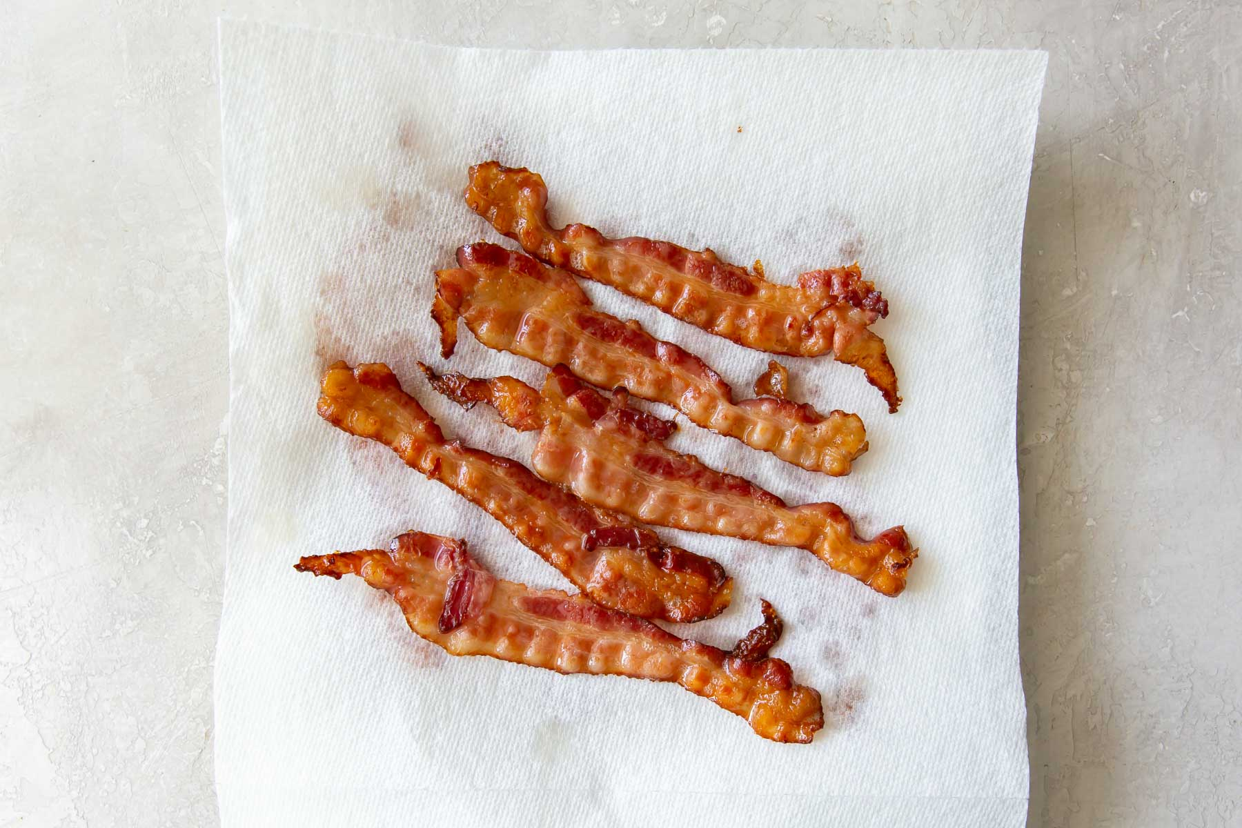cooked bacon slices on paper towel lined plate