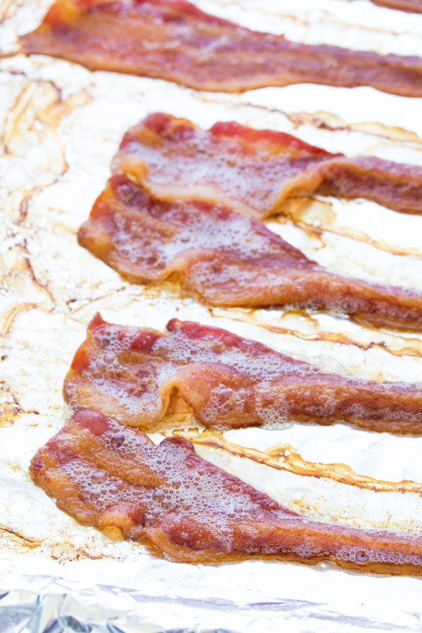 Crispy cooked bacon on a baking sheet pan.