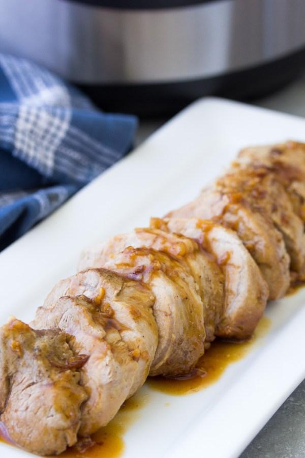 Instant Pot pork tenderloin with honey garlic sauce, sliced on a platter.