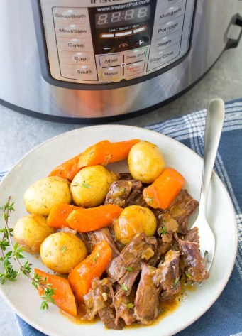 Easy Instant Pot Pot Roast with potatoes and carrots, served on a plate. The beef is so tender!