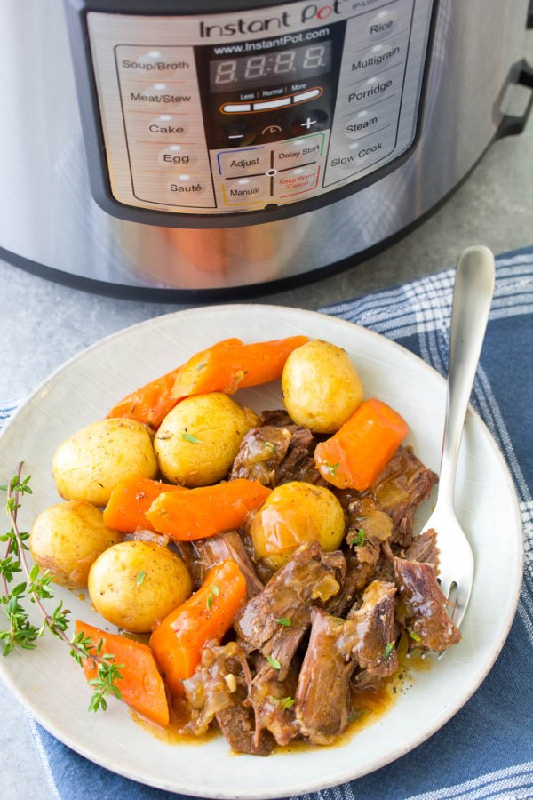 Easy Instant Pot Pot Roast with potatoes and carrots, served on a plate. The beef is so tender after cooking in a pressure cooker!