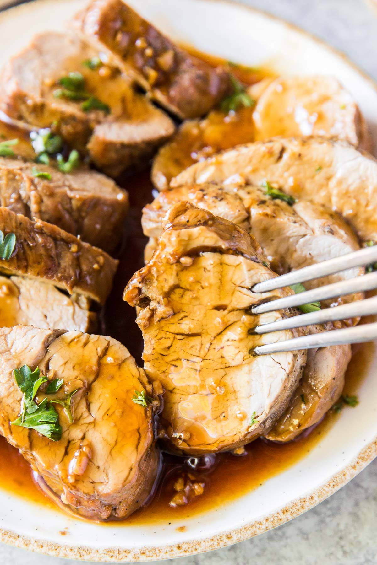 close up of sliced pork tenderloin with sauce and a fork