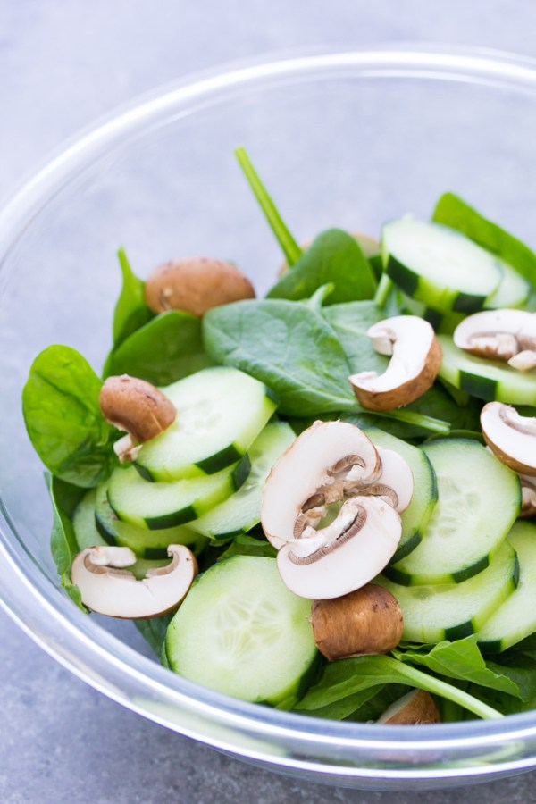 Spinach, cucumber and mushrooms in a bowl to make spinach salad.